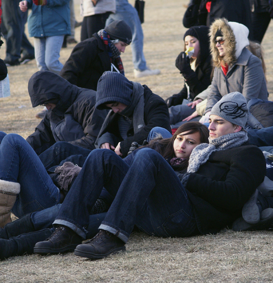 Young America Huddled in Hope: A group of students hunker down against the cold in anticipation of President-Elect Obama's swearing in ceremony near the Washington Monument.  Photo: Luis Trevino, The Military Family Network