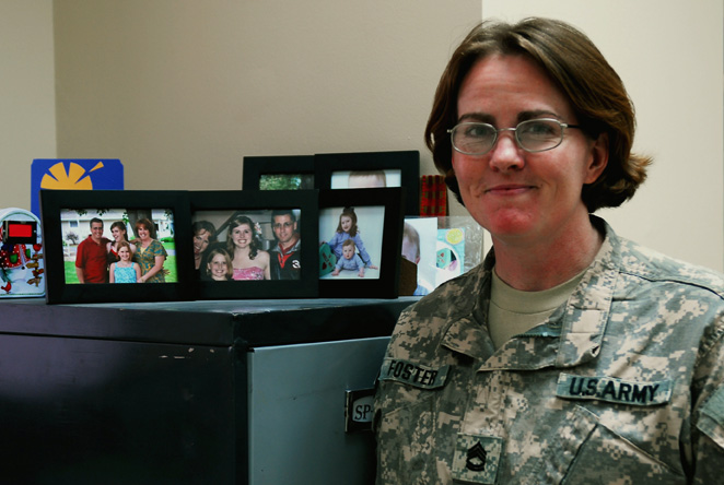 Sergeant First Class Helen Foster, the noncommissioned officer in charge for human resources, Division Special Troops Battalion, 3rd Infantry Division, deployed to Contingency Operating Base Speicher, Tikrit, Iraq, poses next to her Family photos as she thinks about her husband. (U.S. Army Photo by Spc. Jessica Rohr)