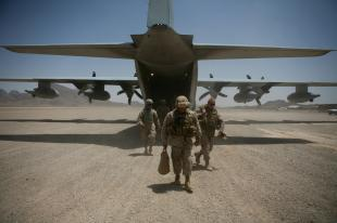 Marines from Marine Expeditionary Brigade-Afghanistan exit an Air Force C-130 after arriving in Farah province, June 8. Brig. Gen. Larry Nicholson, commanding general of MEB-Afghanistan, traveled with fellow key leaders from the Marine base of operations in Helmand province to gauge progress made by the Provincial Reconstruction Team-Farah.  Cpl. Aaron Rooks
