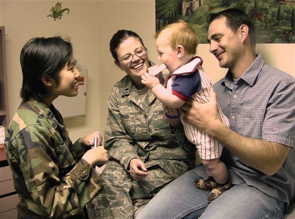 "Air Force Capt. (Dr.) Minh-Thu Le interacts with her patient, 8-month-old Alexander, as he performs the common newborn ritual of ""mouthing the book."" Alexander's parents, Air Force 1st Lt. Alice L. Shepard and her husband, Steven, happily look on at Travis Air Force Base, Calif. U.S. Air Force photo by James Spellman Jr."