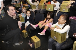 Trevor Romain, award-winning author and children's books illustrator, jokes with military children after a USO-sponsored film screening of the DVD