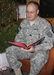 "Army Lt. Col. Stephen Jeselink, Task Force Warrior deputy commander, is recorded while reading the poem ""The Night Before Christmas"" at the USO at Bagram Airfield, Afghanistan, Dec. 16, 2008. Through the United Through Reading military program, the Jeselink family in Louisiana will be able to continue a long-standing holiday tradition of listening to Stephen read the poem on Christmas Eve. U.S. Army photo"