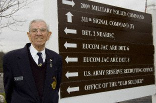 Retired Army Sgt. Maj. Ray Moran stands next to the sign that points to his office at Fort George G. Meade, Md., and uses the nickname he gives to himself and many others,