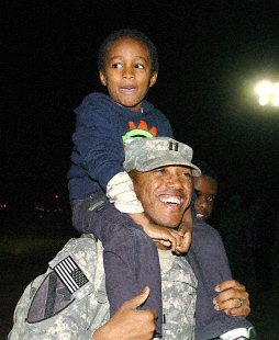 Capt. Eddie Fazaldin, 1st Battalion, 8th Cavalry Regiment, 2nd Brigade Combat Team, 1st Cavalry Division, of Killeen, Texas, carries his 6-year-old brother, Abbas Salim, off Cooper Field, Dec. 19, as he and hundred others return from Iraq. 2nd Brigade Combat Team, 1st Cavalry Division Public Affairs