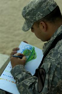 "Sketching a familiar Californian scene, signal support systems maintainer, Pfc. Juan D. Franco, Company C, Division Special Troops Battalion, 1st Cavalry Division, uses heavy blue and greens to ""bleed out the detail"" of his drawing. Franco has been drawing with ink, colored pencil, charcoal, and water colors since elementary school. Franco wants to be more proficient with oil colors and airbrushing before he will consider himself a true artist."