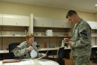 1st Sgt. Dara Wylder (left), acting sergeant major, 1st Air Cavalry Brigade (Rear), 1st Cavalry Division, of Houston, and Maj. Daniel Legereit, of Metropolis, Ill., commander of the 1st ACB (Rear), 1st Cav. Div., inspect paperwork following the activation of the 1st ACB rear detachment, Feb. 12, at 1st ACB headquarters, Fort Hood, Texas.,by Spc. Alun Thomas