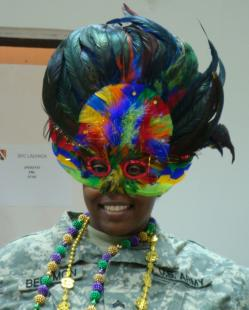 Sgt. RoKeisha Berymon of Alexandria, La., 225th Engineer Brigade, Louisiana National Guard, celebrates Mardi Gras, Feb. 24, in style by dressing up in the traditional holiday attire of colored beads and masks, 225th Engineer Brigade