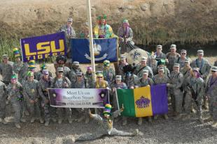 "Members of the Louisiana National Guard's 225th Engineer Brigade pose in front of their headquarters, Feb. 24. The Soldiers won't let a deployment to Iraq stand in their way to celebrate Mardi Gras. Donations from home and a ""joie-de-vive"" keeps the good times rolling. ,225th Engineer Brigade"