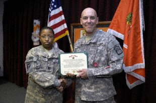 U.S. Army Capt. Judy Hobson, 25th Signal Battalion, Headquarters and Headquarters Detachment commander, and Sgt. 1st Class Evan Roberts from Somerset, Pa., pose for a photograph following a Bronze Star award ceremony at Camp As Sayliyah, Qatar, Feb. 22. While deployed to Afghanistan, Roberts increased communication efficiency between U.S. and coalition forces on the Pakistan-Afghanistan border. He has built radios for over 40 years.