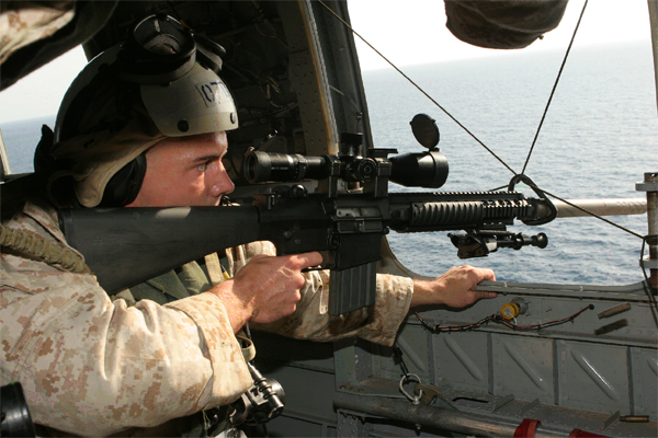 A scout sniper from Battalion Landing Team 2/6, 26th Marine Expeditionary Unit, fires his MK-11 sniper rifle at floating targets from a window of a CH-46E Sea Knight helicopter Sept. 27, 2009, in the Gulf of Aden. The 26th MEU and Iwo Jima Strike Group are currently deployed in the Central Command area of responsibility. (Official USMC photo by Cpl. Aaron J. Rock)