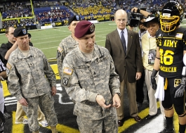 Staff Sgt. Jason T. Fetty flips the coin to start the 2009 All-American Bowl in the Alamodome in San Antonio, Texas. Fetty is a civil affairs NCO at Fort Bragg, N.C., and was one of 85 Soldier-Heroes representing the Army during pre-game activities. Sergeant Major of the Army Kenneth O. Preston, Army Vice Chief of Staff Gen. Peter W. Chiarelli, and Secretary of the Army Pete Geren assisted in the ceremonial toss. Photo by Benjamin Faske