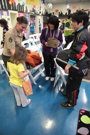 Staff Sgt. Cheryl L. King and her daughter, Ava, receive a gift from Naoya Murakami and Saya Onodera Jan. 11 at the Camp Foster Youth Center. Twenty-four children and six chaperones from Oshima Island are participating in the youth cultural exchange and homestay program. The students from Oshima prefecture are staying with military families that volunteered to host them during their visit on Okinawa. King is the training chief with S-3, training and operations, Marine Wing Headquarters Squadron 1, 1st Marine Aircraft Wing, III Marine Expeditionary Force. Murakami and Onadera are both students on Oshima Island, which was affected by the Great East Japan Earthquake and subsequent tsunami in March 2011. (U.S. Marine Corps photo by Lance Cpl. Daniel E. Valle/Released)