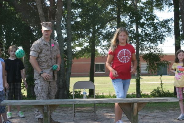 CAPE CARTERET, NC (June 2, 2009) – Cpl. Michael Clawson of 2nd Battalion, 6th Marine Regiment, 2nd Marine Division  participates in a ball toss challenge against fourth-grader Sarah Staeble at White Oaks Elementary, 2 June 2009.  Marines from 2/6 volunteered at the White Oaks Elementary field meet. (Official USMC photo by Cpl. Jesse J. Johnson)