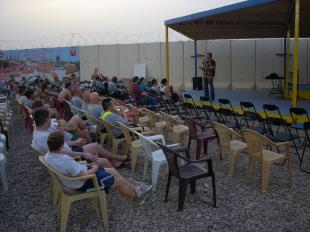 Comedian George Grey warms up the crowd on a stage located at the pool facility on Contingency Operating Base Q-West, Iraq, June 11. Los Angeles-based comedians George Grey, Bruce Jingles, and Joey Medina performed for more than 160 Soldiers, Airmen and contractors at the opening of the