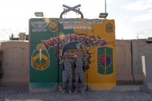 Spc. Vincente Oliver (left) and his father, Sgt. Thomas Krumpfer (right), both assigned to 267th Military Police Company, 93rd MP Battalion, 8th MP Brigade, Multi-National Division - Baghdad, stand in front of their brigade's headquarters on Camp Liberty, Iraq, June 2. The Cumberland City, Tenn. natives deployed with the Dickson, Tenn., based 267th MP Co. earlier this year.  Spc. Charles Iavarone