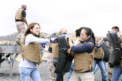 Military spouses Cynthia Mass and Anita Flores, get a taste of the Marine Corps Martial Arts Program during SOI's Jane Wayne Day, June 13. The Marine Corps Martial Arts Program is a combat system developed by the United States Marine Corps that combines hand-to-hand and close-quarters combat techniques. Cpl. Alvaro Aro