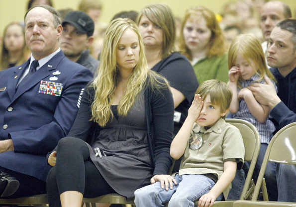 (BETH SCHLANKER/Standard-Examiner) Jase Spargur, 6, wipes away a tear as he sits with his mom, Lindsey, and his maternal grandfather, retired Air Force Chief Master Sgt. David Spargur, during a ceremony to award his late father with the Silver Star.