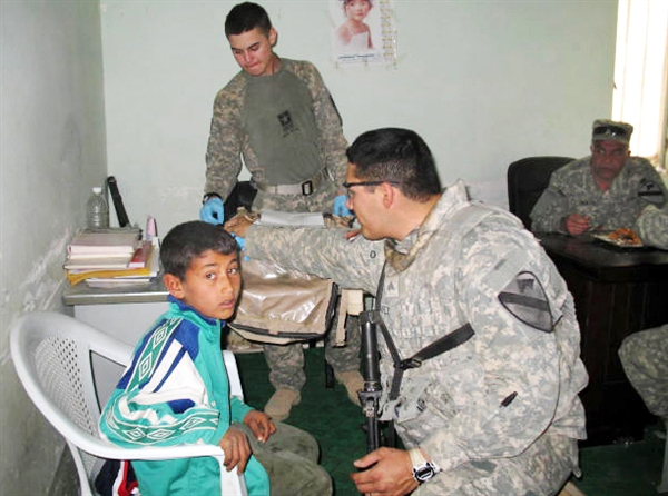 Army Sgt. Ray Chavez and Army Pfc. Jonathon Ahrem treat an Iraqi boy during a joint U.S.-Iraqi humanitarian mission in Iraq's Maysan province, March 8, 2009. U.S. Army photo by Sgt. 1st. Class Mark Schenk