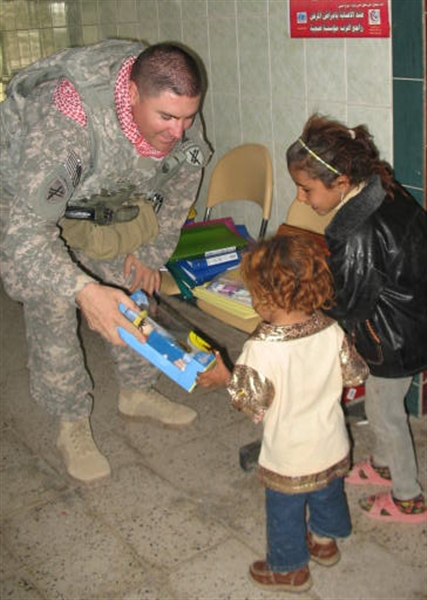Army Sgt. Ray Chavez passes out toys to Iraqi children during a joint U.S.-Iraqi humanitarian mission in Iraq's Maysan province, March 8, 2009. U.S. Army photo by Sgt. 1st. Class Mark Schenk