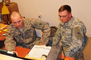 Army Sgt. Timothy Kettlewell, a volunteer from Headquarters Company, 81st Brigade Combat Team, Washington Army National Guard, who helped get the Camp Ramadi testing and education center started, helps Army Sgt. Nicholas Benfield, also from HQ Co., 81st BCT, navigate through his education choices at the center on April 26.