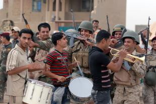 A small band, along with soldiers of the 45th Iraqi Army Brigade, celebrate a goal by the home team during the Combined Forces Football Tournament, in the Salman Pak community, May 10. The game was met with enthusiasm and support from the local community, who showed up to watch the game.  Sgt. Joshua Risner