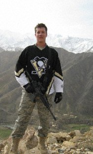 Air Force 2nd Lt. Jason Smith, Provincial Reconstruction Team Panjshir Public Affairs officer, dons a Pittsburgh Penguin jersey after climbing a large hill near Forward Operating Base Lion in the Panjshir Province of Afghanistan. Smith, a Pittsburgh native and Penguin fan, will be deployed to Afghanistan for almost a year where he will work to security, governance and reconstruction efforts. (Photo by U.S. Army Capt. Benjamin Fitting, PRT Panjshir executive officer)