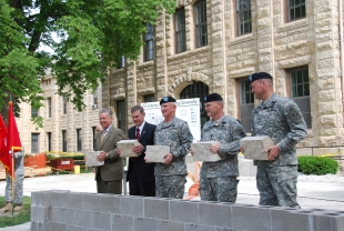 Participants prepare to lay stones during a ceremony May 20 in front of Building 68 at Rock Island Arsenal, Ill. The building is the future home of First Army headquarters and the ceremony marked the completion of the first phase of construction. From left are: Jim Russell, CEO of Russell Construction; Joel Himsl, Rock Island garrison manager; Lt. Gen. Thomas G. Miller, First Army commander; Maj. Gen. Yves Fontaine, commander of the U.S. Army Sustainment Command; and Col. Keith Landry, commander of the U.S. Army Corps of Engineers' Louisville branch.
