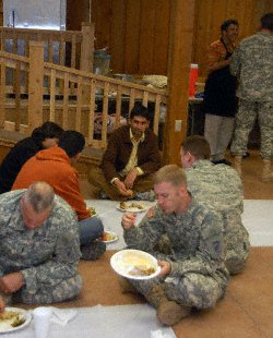 Rahman Arman, the lead instructor for the Afghan language and culture seminars given to Provincial Reconstruction Teams at Camp Atterbury, sits with the troops as they partake in a traditional Afghan meal coordinated by the 189th Infantry Brigade here through Indiana University. The PRTs participated in the luncheon as part of their cultural awareness training Nov. 14 at Camp Atterbury Joint Maneuver Training Center. T.D. Jackson