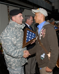 Gen. Peter W. Chiarelli, the Army's vice chief of staff, presents a flag flown over Ground Zero in New York to Army Sgt. Joel Dulashanti after a brief ceremony at the site for a group of wounded veterans. The ceremony was part of a United Service Organizations-Microsoft