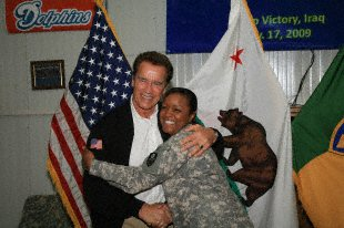 California Governor Arnold Schwarzenegger hugs soldier for photograph during his visit to the California-native 49th Military Police Brigade, Nov. 17.