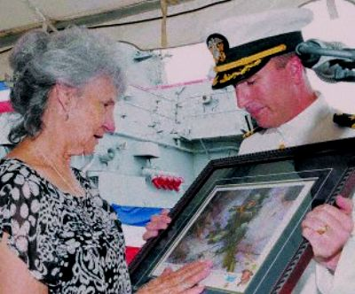 Cmdr. Brian Fort, commanding officer of the Arleigh Burke-class guided-missile destroyer USS Gonzalez, presents Dolia Gonzalez with a painting of her son, Marine Corps Sgt. Freddy Gonzalez, before turning command of the ship over to Cmdr. Lynn Acheson at Naval Station Norfolk. The ship is named after Sgt. Freddy Gonzalez and the ship' crew commissioned the painting as a gift for Dolia Gozalez' upcoming 80th birthday. Petty Officer 1st Class Michelle Lucht