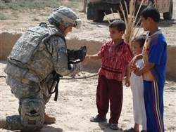 Army Pfc. Serena Norman, a medic with Company C, 589th Brigade Support Battalion, 41st Fires Brigade, tends to Iraqi children during a mission in Kut, Iraq, Sept. 19, 2008. U.S. Army photo by Staff Sgt. Daniel Bishop