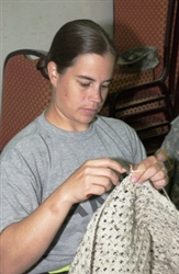 Army Staff Sgt. Lani Yearicks, a native of Gwinn, Minn., assigned to the 10th Mountain Division Band, crochets a prayer shawl Sept. 21, 2008, at Camp Victory, Iraq. U.S. Army photo by Spc. Tiffany Evans, Multinational Division Center
