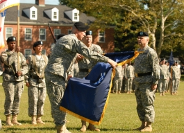 """With Maj. Gen. Alan D. Bell holding the 99th RSC's colors, 99th Command Sgt. Maj. Kurtis J. Timmer carefully unrolls them, revealing the 99th's """"Checkerboard"""" patch."""
