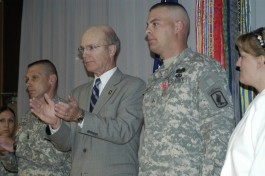 """Secretary of the Army Pete Geren (second from left) leads the applause for Cpl. Jonathan James after awarding him the Bronze Star Medal with """"V"""" device for his action during Operation Enduring Freedom in Afghanistan, where he helped defeat an enemy ambush."""