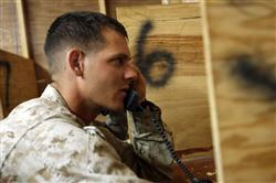 Cpl. Ryan D. Marmon, 20, a vehicle commander with Headquarters and Support Company, 3rd Battalion, 7th Marine Regiment, Regimental Combat Team 5, from Houston, calls home to his friends at the Morale, Welfare and Recreation Center at Camp Hit, Iraq, Oct. 14. The MWR Center features numerous phones and computers that Marines can use to stay connected to their loved ones during their deployment to Iraq.