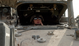 Spc. Tiffany Knotts peers out from the driver's hatch while performing her weekly Preventative Maintenance Checks and Services on her Stryker vehicle Oct. 13 at Camp Taji, northwest of Baghdad.