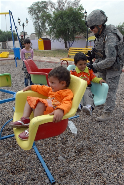 Army 1st Lt. Rosita Rodriguez pushes two Iraqi children on a ride at the Oct. 28, 2008, grand opening of Dover Park in the Qahira neighborhood of Baghdad's Adhamiyah district. U.S. Army photo by Sgt. Jerry Saslav