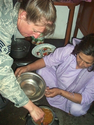 Air Force Staff Sgt. Michelle Cooper, services superintendent for the Panjshir Provincial Reconstruction Team, helps to prepare a special meal. Miriam Panjshiri, director of women's affairs for Afghanistan's Panjshir province, and her sister, Nasrene, hosted the PRT's affairs team for a time of fellowship and an Afghan cooking class Oct. 2, 2008. U.S. Army photo