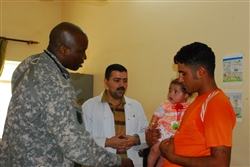 Army Capt. (Dr.) Nkemakonam Okpokwasili, a 41st Fires Brigade physician, confers with an Iraqi doctor about a girl's condition at a combined medical effort in Hayy, Iraq, Oct. 9, 2008. U.S. Army photo by Sgt. 1st Class Joe Thompson