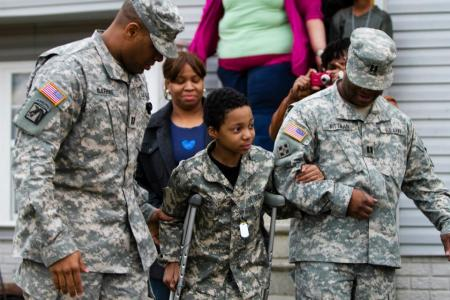 Army Reserve captains John Barbee and Sherman Pittman assist Khalil Quarles, 10, down the sidewalk outside his home during a surprise visit from members of the 200th Military Police Command and the Office of the Chief, Army Reserve.