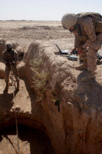 The 2nd Battalion, 3rd Marine Regiment's Cpl. Tavares Taylor lowers a reconnaissance robot into an 80-foot karez as Markbot operator Cpl. Garrett Andrews guides it with the remote controller Sept. 23, 2009. The Marines were investigating tunnels in the district's karez system - a network of wells and tunnels hundreds of years old - that are suspected to have been used by insurgents as caches for IED making materials. Gunnery Sgt. Chris W. Cox
