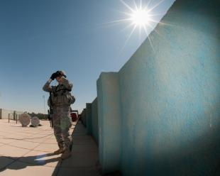 Sgt. Deny Caballero, an infantry team leader with Company B, 2nd Battalion, 504th Parachute Infantry Regiment, 1st Brigade Combat Team, 82nd Airborne Division (Advise and Assist Brigade), stands watch on the roof of an Iraqi police station in Ramadi, Iraq, during a key leader engagement, Sept. 25. Caballero and his wife, Catilina Caballero, are both deployed with the brigade, but on different forward operating bases in Al Anbar province. Spc. Michael MacLeod