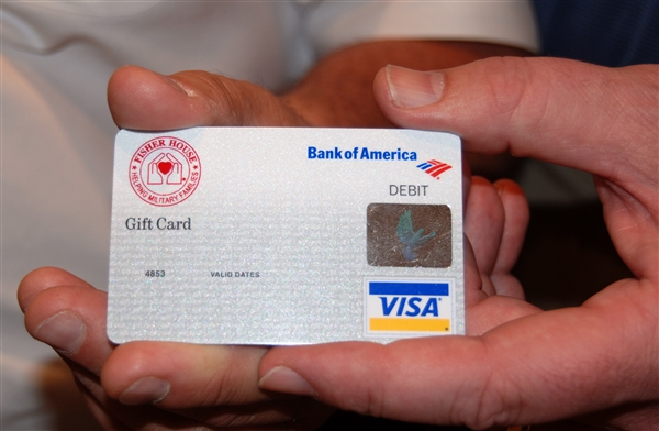 A Bank of America Visa debit card bearing the Fisher House Foundation logo is displayed during a ceremony to present the first 400 such cards to the Brooke Army Medical Center Fisher Houses on Fort Sam Houston, Texas. Through a new partnership, Bank of America's Military Segment has agreed to cover processing and other fees associated with purchasing gift cards, thereby stretching the Fisher House Foundation's donors' dollars. Photo courtesy of the Fisher House Foundation