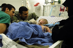 Al Amreeki, a 3-year-old Iraqi burn victim, is surrounded by Air Force Capt. Michael Riegler (left), a 332nd Expeditionary Medical Operations Squadron nurse; Basem Hadi, an Iraqi interpreter; and his mother, Amil, before a medical evacuation flight March 19, 2008, from the Air Force Theater Hospital at Balad Air Base, Iraq, to the United States. U.S. Air Force photo by Tech. Sgt. Jeffrey Allen