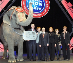 Asia, one of Ringling Bros. and Barnum and Bailey Circus' elephants, shows her support of the military by sporting an America Supports You dog tag, held by former chairman of the Joint Chiefs of Staff retired Air Force Gen. Richard B. Myers. The duo was joined by: (from left) Mary Jo Myers; Kenneth Feld, chairman of the circus; his wife, Bonnie, and daughter Nicole Feld; and Allison Barber, deputy assistant secretary of defense for internal communications and public liaison. Photo by Samantha L. Quigley