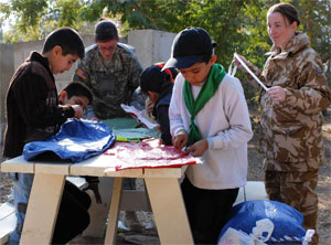 Iraqi children, under the guidance of coalitian forces, make sit-upon pillows during the day