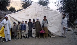 Task Force Saber soldiers have supplied a tent for these Afghan students and their teacher. Very few schools in Afghanistan's Kunar province have buildings. Photo by Capt. Jay VanDenbos, USA