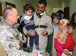 Navy Cmdr. Steven Frost chats with families at a newly opened primary health care facility in Iraq. Photo by Norris Jones