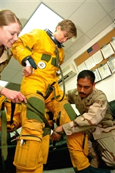 Air Force Capt. Heather Fox, a U-2 Dragon Lady pilot with 99th Expeditionary Reconnaissance Squadron, stands while Senior Airman Roric Ongaco (right) and Staff Sgt. Lisa Tetrick, 99th ERS physiological support division technicians, help attach the torso harness to her suit. Fox is one of only three woman U-2 pilots currently serving in the Air Force. Photo by Senior Airman Levi Riendeau, USAF